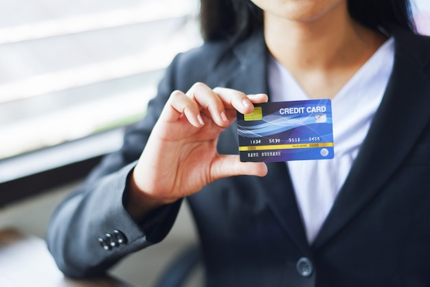 Manos de mujer con tarjeta de crédito para compras en línea en una oficina / gente de trabajo que paga tecnología en línea billetera dinero pago