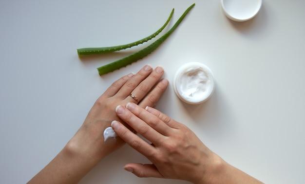 Manos de mujer tarro blanco con crema y hojas de aloe sobre un fondo blanco.