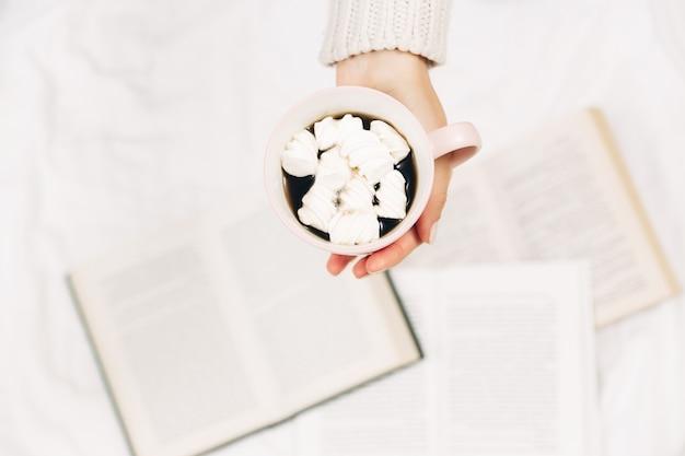 Manos de mujer con taza de café y libros. elegante foto minimalista. vista superior.