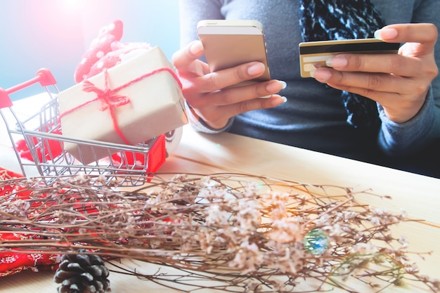 Manos de mujer con teléfono inteligente y tarjeta de crédito. compras en línea de vacaciones