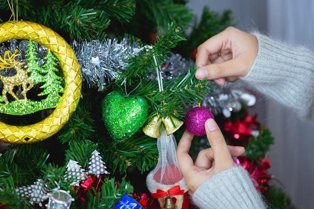 Las manos de la mujer está tocando el adorno de navidad
