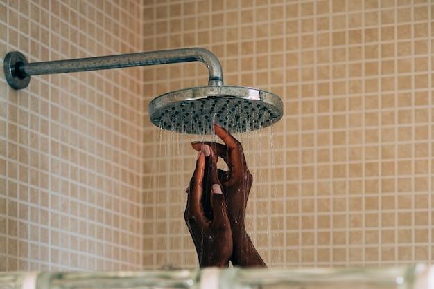 Manos de mujer tomando una ducha