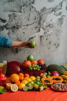 Manos de mujer tomando una manzana verde de una mesa con una gran variedad de frutas y verduras orgánicas frescas.