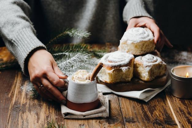 Manos de mujer tomando una taza de chocolate caliente con crema batida y un bollo de navidad.