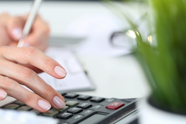 Manos de mujer trabajando en la calculadora de cerca