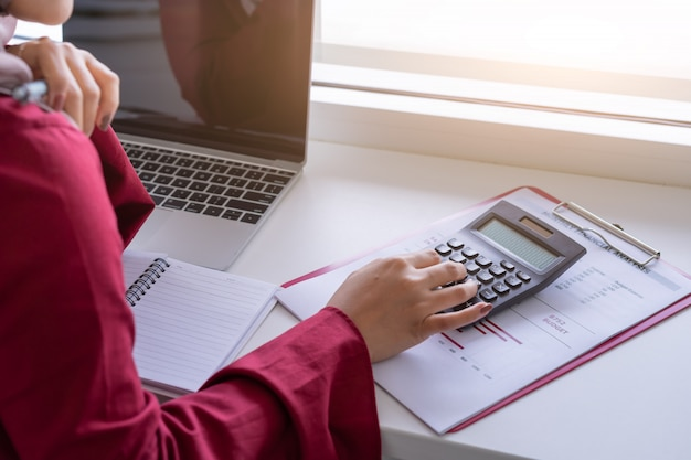 Manos de mujer trabajando con calculadora sobre planificación financiera personal en café.