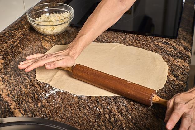 Manos de mujer trabajando en una masa de pizza