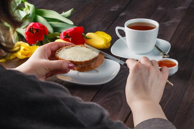 Manos de mujer untando pan