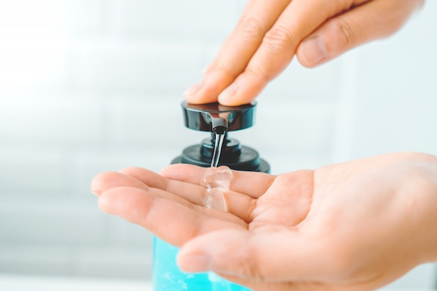 Manos de mujer usando alcohol gel desinfectante para manos con lavado limpio