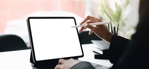Manos de mujer usando laptop con pantalla en blanco en un escritorio de oficina