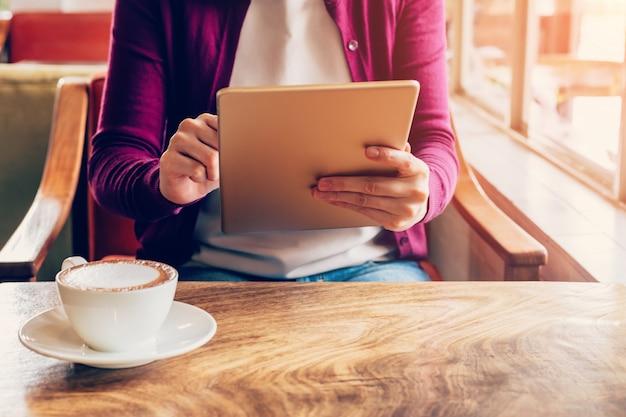 Manos de mujer usando y sosteniendo la tableta de la computadora en cafetería con vintage entonado.
