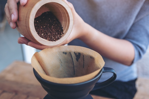 Manos de mujer vertiendo café molido del molinillo de madera en un filtro de café por goteo
