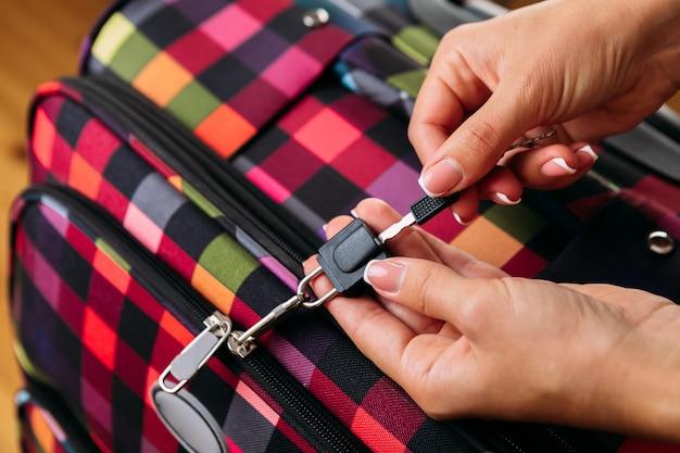 Las manos de las mujeres abren una maleta con cosas. concepto de viaje
