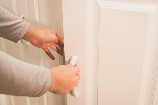 Las manos de las mujeres abren la puerta del armario / del gabinete, puerta de madera blanca