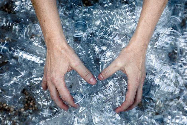Manos de mujeres agarrando botellas de plástico para recogerlas y tirarlas a la basura