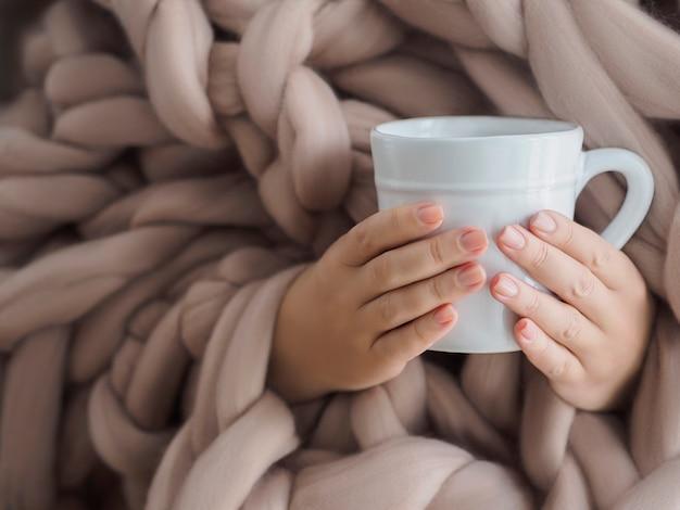 Las manos de las mujeres en una cálida manta de lana merino con una taza de café.