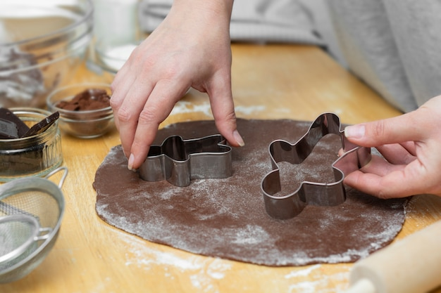 Las manos de las mujeres cocinar festivas galletas de jengibre de navidad. cocinar galletas de chocolate o postre.