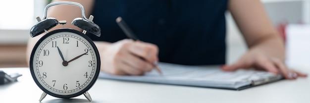 Manos de mujeres escriben en el documento.