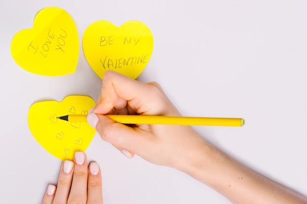 Las manos de las mujeres escriben una nota de amor en corazones de nota iluminadores para el día de san valentín.