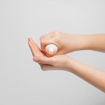 Las manos de las mujeres exprimen la crema de un tubo para hidratar las manos.