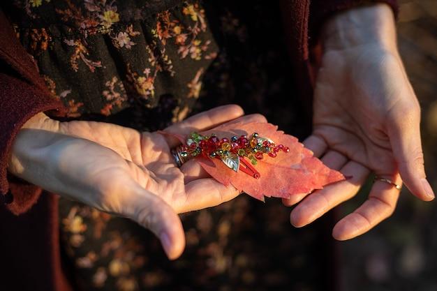 En manos de mujeres hay una hoja otoñal de otoño y un accesorio para el cabello de cuentas de vidrio.