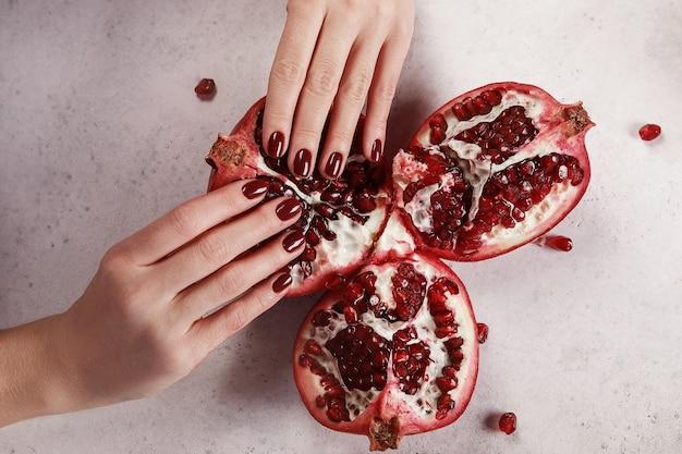 Manos de mujeres hermosas con manicura rojo oscuro, fondo blanco, sosteniendo una granada madura. extensión de uñas. manicura, salón spa. creativo, publicitario.