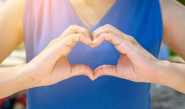 Las manos de mujeres y hombres tienen forma de corazón con la luz del sol que pasa a través de las manos.