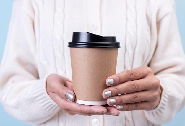 Las manos de las mujeres se llevan la taza de café de papel maqueta para mensajes de texto publicitarios creativos o contenido promocional.