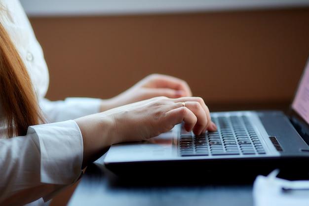 Las manos de las mujeres mecanografían una computadora portátil en el teclado, primer. lugar de trabajo