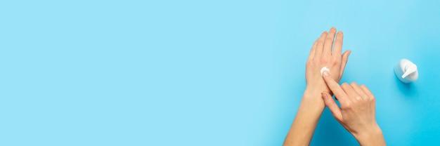 Manos de mujeres. la mujer mancha la crema en su mano en un azul. concepto de cosmética, cuidado de la piel, loción, maquillaje, spa.