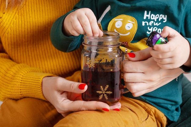 Manos de mujeres y niños sosteniendo una taza de té. tiempo de fiesta. tarro de té con bebida