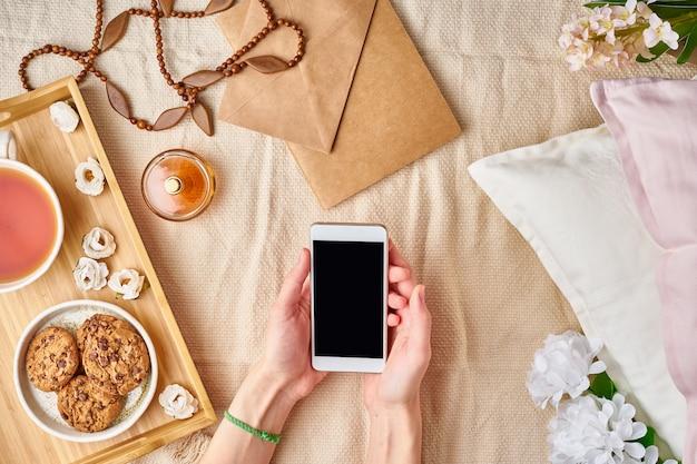 Manos de las mujeres planas que sostienen un teléfono inteligente. acogedor hogar descanso, vacaciones, fin de semana.