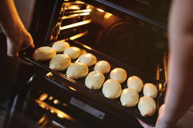 Las manos de las mujeres ponen en el horno una bandeja para hornear con pasteles de levadura cruda