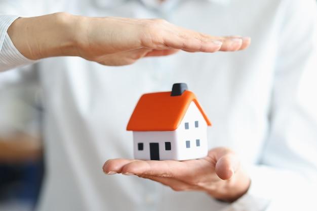 Las manos de las mujeres salvan casa con concepto de techo