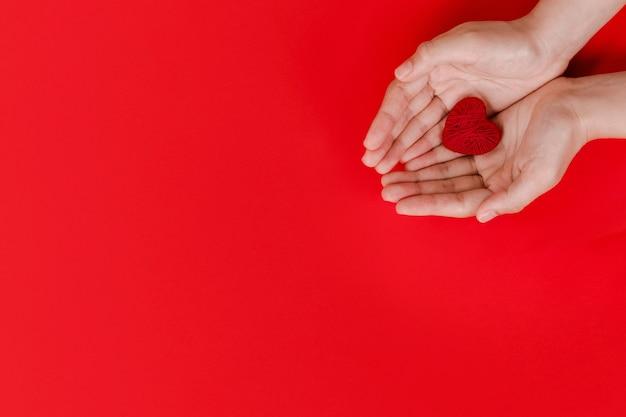 Manos de mujeres sosteniendo corazón rojo sobre rojo
