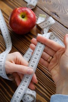 Manos de mujeres sosteniendo una ruleta, junto a una manzana. el concepto de dieta, nutrición saludable.