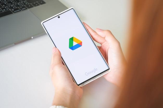 Manos de mujeres sosteniendo samsung note 10 plus con aplicaciones de google drive en pantalla.