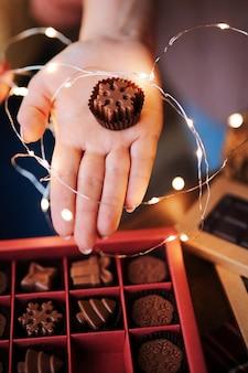 Las manos de las mujeres sostienen una hermosa caja navideña con chocolates de leche natural hechos a mano en forma de copos de nieve.