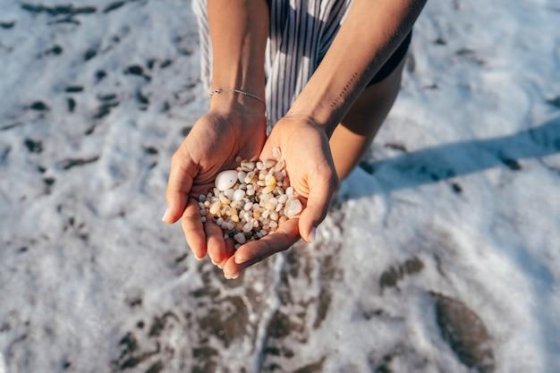 Las manos de las mujeres sostienen muchas piedras pequeñas