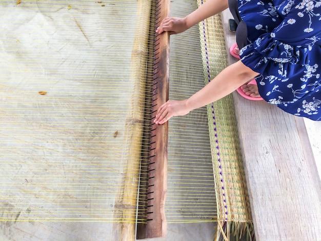 Las manos de las mujeres tejidas esteras tradicionales son productos hechos a mano en el campo de tailandia.