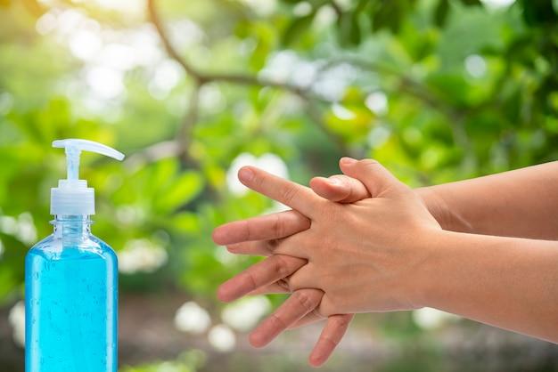 Las manos de las mujeres usan gel de alcohol, lavándose las manos para protegerse contra virus infecciosos, bacterias, gérmenes y covid-19.