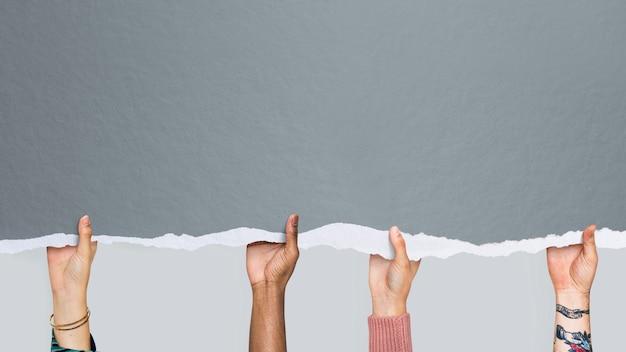 Manos multiculturales sosteniendo un papel tapiz de papel de maqueta gris