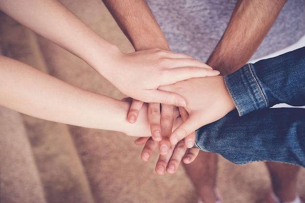 Manos multiétnicas de jóvenes adultos juntando las manos, concepto de trabajo en equipo de voluntarios y caridad