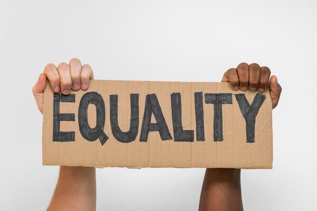 Manos multirraciales sosteniendo cartón con igualdad
