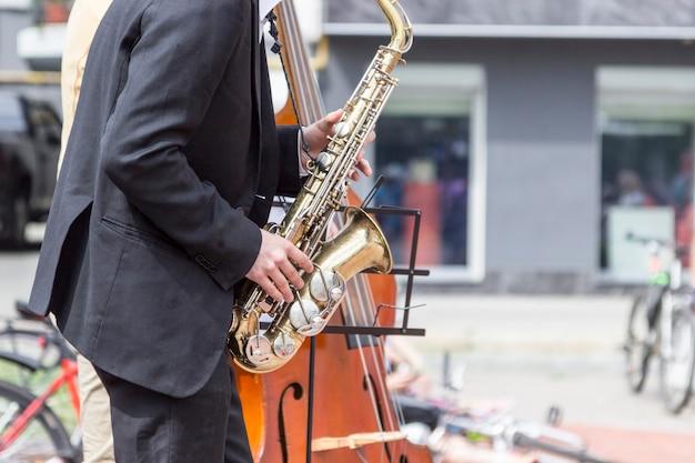 Manos de músico callejero tocando saxofón y contrabajo en un entorno urbano