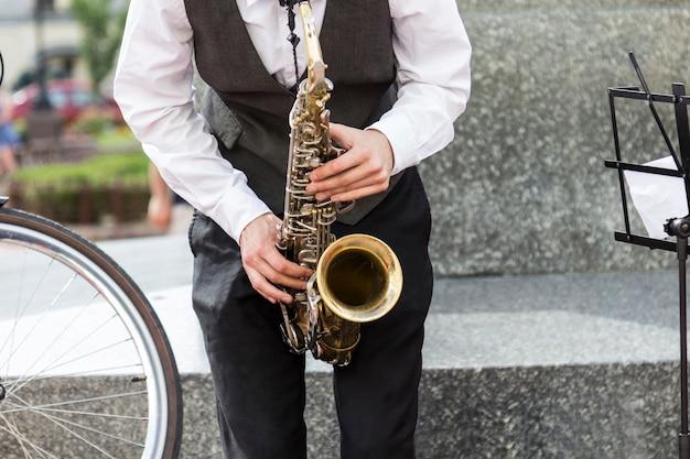 Manos del músico callejero tocando el saxofón en un entorno urbano