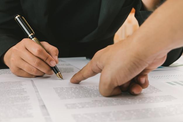 Manos de negocios señalando y términos de la firma y contrato de documentos de contrato de contrato, iniciando