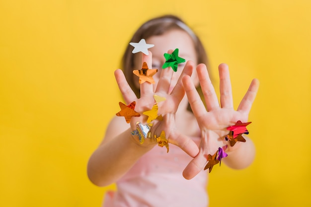 Manos de una niña con confeti multicolor en manos