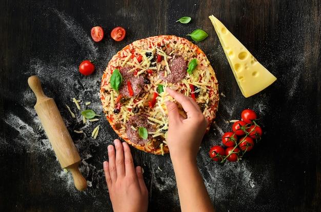 Manos de niña haciendo, decopando, preparando pizza con hojas de albahaca en la oscuridad. vista superior, copia espacio