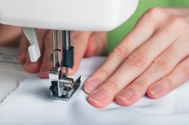Manos, de, niña joven, en, máquina de coser